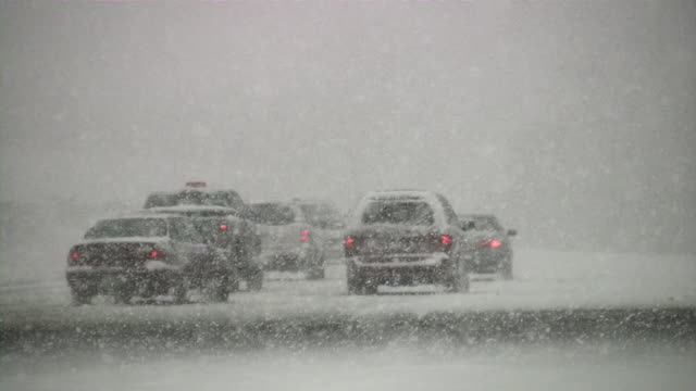 Snowstorm. Winter traffic. Cars on slippery road. Snowfall, snowflakes.