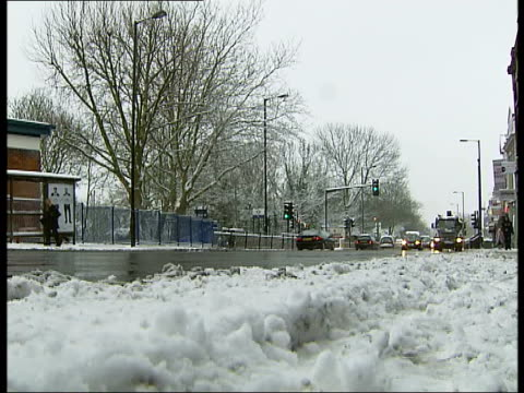 London Barnet Cars parked in snowy suburban street Tyre stuck in snow then car shuffling through snow from car park More of suburban street including...