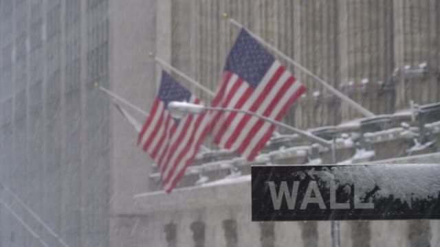 Snowy Street sign of Wall Street and shaking American flags during the snowstorm at New York Stock Exchange on Feb. 09 2017.