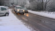 Snowy traffic conditions in Hampshire ENGLAND Hampshire Various of cars abandoned on snowy verge of A road / driver 'reclaiming' his carscraping off...
