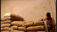 threat to Asian countries India and Thailand Sacks of rice carried into storeroom and stacked / bowls of different types of rice displayed / stalls...