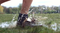 CU SLO MO Soccer boots running through puddle / Manchester, United Kingdom