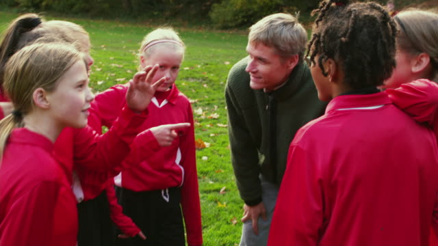 MS DS Soccer coach huddles up team before game / Portland, Oregon, USA
