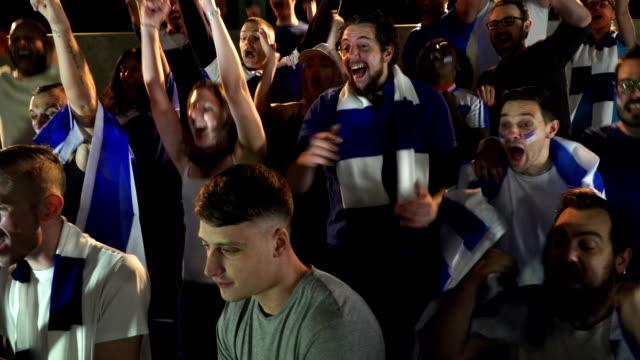 4K: Soccer / Football fans en supporters in stadion viert doelpunt wordt