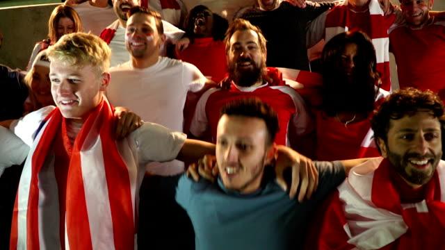 Voetbal / voetbalfans in het stadion springen arm in arm - Super slow motion