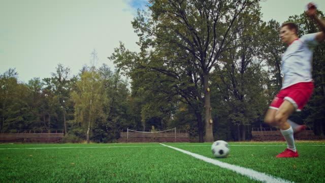 Soccer player dribbles ball in stadium
