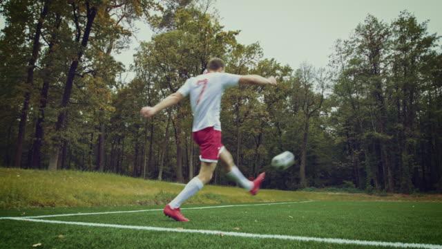 Soccer player kicks ball in stadium