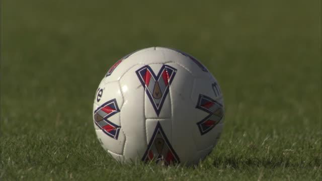 CU Soccer player placing ball on field, then kicks it / Sheffield, England, UK