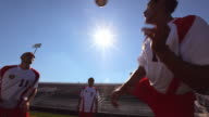 Three soccer players practice head-butting and kicking a soccer ball.