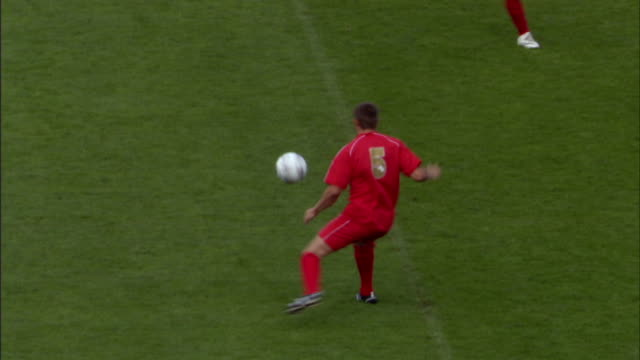 HA WS Soccer players kicking ball and running around field during game/ Sheffield, England