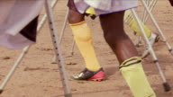 Soccer players walk around a dusty pitch on crutches. Available in HD.