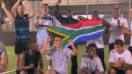MS Soccer team holding South African flag and cheering, London, UK