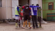 A soccer team of amputees huddles in a circle. Available in HD.
