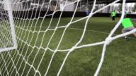 MS Soccer team scoring goal, seen from behind goal post, London, UK
