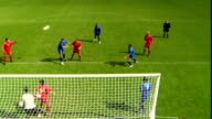 HA WS Soccer teams passing ball around in front of goal/ Red team player kicking ball into goal/ ZI MS blue team member yelling at goalie/ Sheffield, England