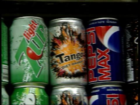London GIR i/c Cans of 7up 7up Light Tango Diet Orange Pepsi Max Tango on shelf of fridge PAN Hand opening fridge door picking up a number of cans...