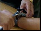 Maxine Carr may be freed ITN Electronic tag being fitted to wrist of man CMS Tag and equipment used to monitor the tag