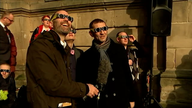 Solar eclipse across the UK and Europe ENGLAND West Midlands Birmingham Crowds gathered in city centre sun partly obscured by clouds above Man...