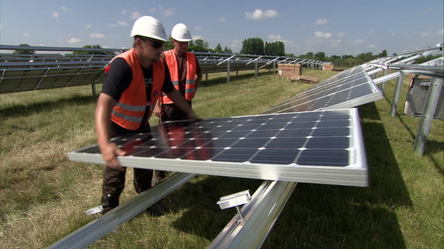 MS solar panel being manually lifted into place by model then adjust into postion by second model / Howbery, Oxfordshire, United Kingdom
