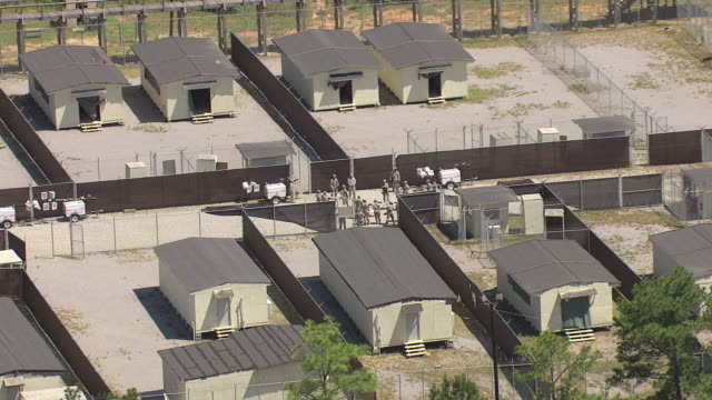 CU AERIAL soldier bunkers lined up with soldiers working outside and pull out to reveal MS of military post Camp Shelby / Mississippi, United States