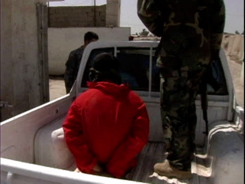 Soldier entering back of pickup truck next to suspect detained by Iraqi Army / Mahmudiyah Iraq / AUDIO
