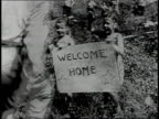 Soldier greeting family on street / Soldier embracing woman as crowd watches / Soldier greeting children holding Welcome Home sign / Buildings under...
