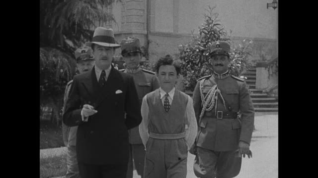 ALBANIA Soldier guarding gate King Zog's palace Soldiers on palace grounds King Zog walking w/ nephew heir Tati EXT INT Hotel w/ tourists