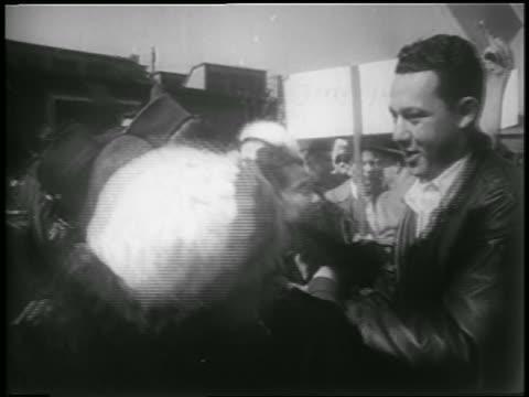 B/W 1953 soldier hugging woman in crowd outdoors / Korean War homecoming