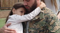 Soldier in wheelchair embracing little daughter