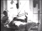 W soldier lying in hospital bed with leg in traction sitting up drinking from a cup and demonstrating movement of leg up and down small American flag...