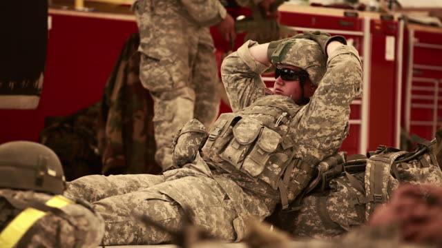 A Soldier lying on the ground, waiting at a hangar.