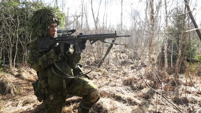 A soldier of the Estonian Defence Forces fires his machine gun to defend his position during a joint military combat exercise with US Army troops on...