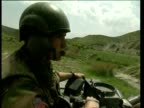 Soldier on tank as it drives down dirt road pan right to reveal dirt road Albania 1999