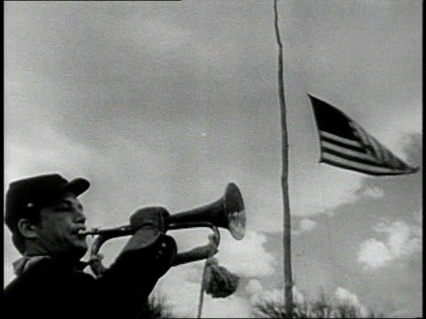 REENACTMENT Soldier playing trumpet while the American flag is raised / United States