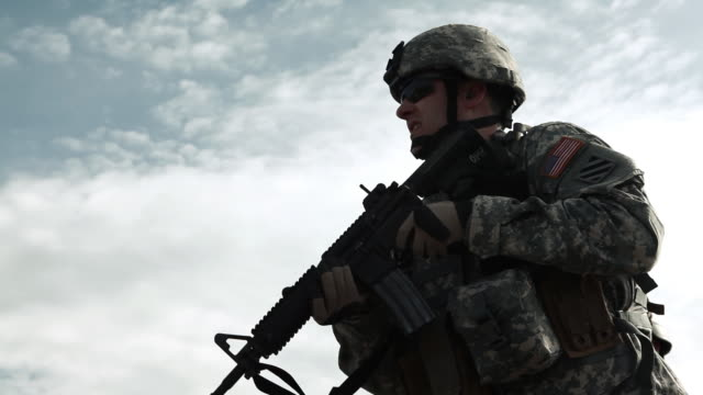 Soldier practicing firing against sky background