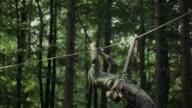 1967 MS PAN MONTAGE WS LA Soldier pulling himself on rope between trees
