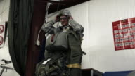 Soldier putting on glasses and strapping on helmet before parachuting.