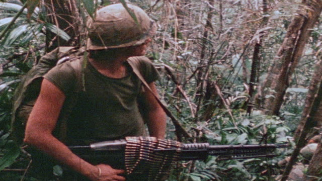 Soldier standing in jungle holding M60 machine gun with ammo belt draped atop / Vietnam