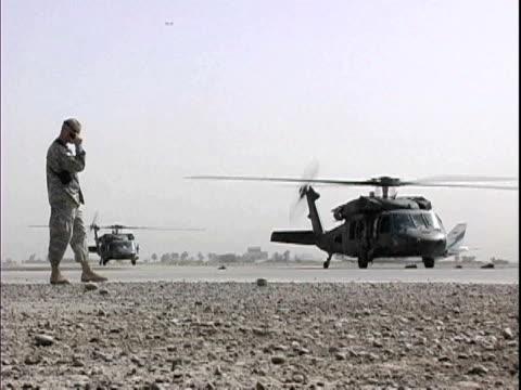 Soldier talking on walkietalkie near Blackhawk military helicopters at Baghdad Airport / Baghdad Iraq / AUDIO