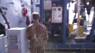 A soldier walks through a submarine and climbs stairs.