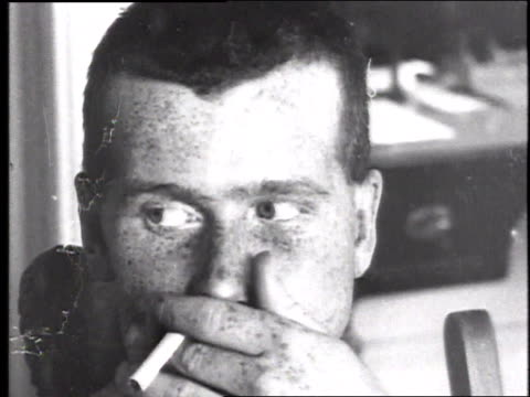 A soldier with a scarred damaged mouth smoking a cigarette by inhaling through his nose and blowing the smoke out of his mangled mouth / France
