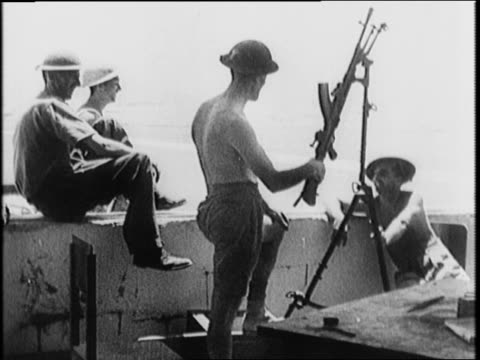 Soldier writes Tobruk in the sand with stick / soldiers on guard others swimming / montage of armed British troops around the city / wrecked Axis...