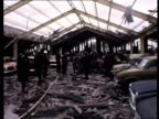 Soldiers and firemen inspect a car showroom following a car bomb explosion