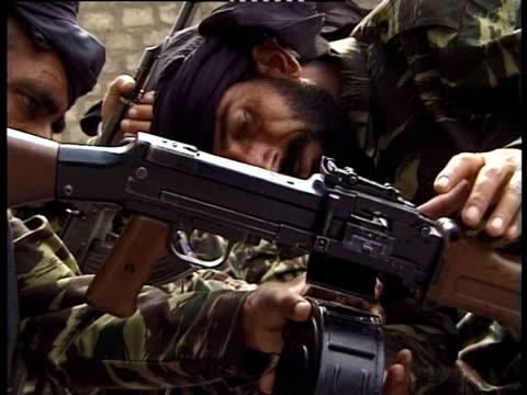 Soldiers attaching ammunition to gun