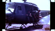 / Soldiers disembarking from Huey helicopter Huey flying away