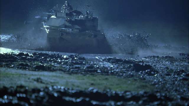 MS, PAN, CU, SLO MO, Soldiers driving tanks through mud in rain at night, USA