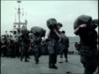 soldiers emerging from a landing craft / soldiers carrying duffel bags and equipment / senior officer addressing troops