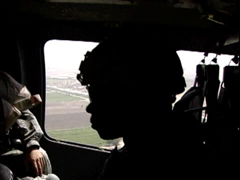 US soldiers flying in military helicopter and looking out window / Baghdad Iraq / AUDIO