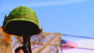 Soldier's gun holding up helmet, low angle close up