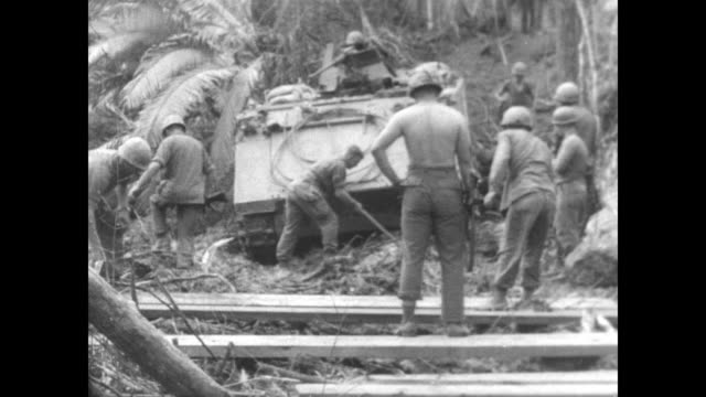 Soldiers in tank push through jungle in Vietnam near the Cambodian border / soldiers using axes create makeshift log road to ease tank's journey...